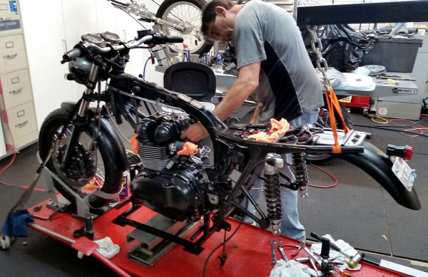 Bill Gately lining up the 1100cc engine on a jack for bolting back onto the frame.