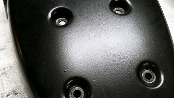 Close up view of untouched rear seat panel orange peel in painted finish.